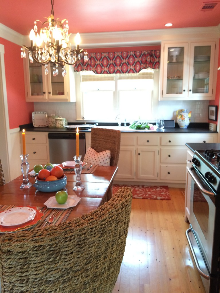 kitchen with white cabinets and coral orange walls ceiling